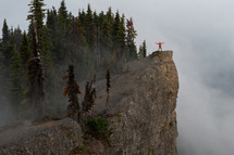 a person with outstretched arms standing on a mountain peak