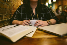 woman reading a Bible and journaling in a coffee shop