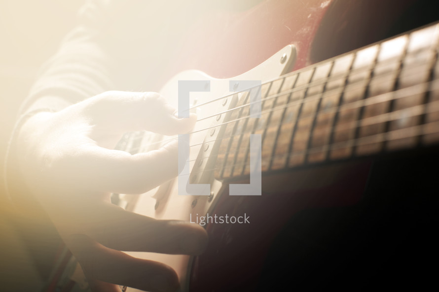 hand strumming a guitar with a bright light.