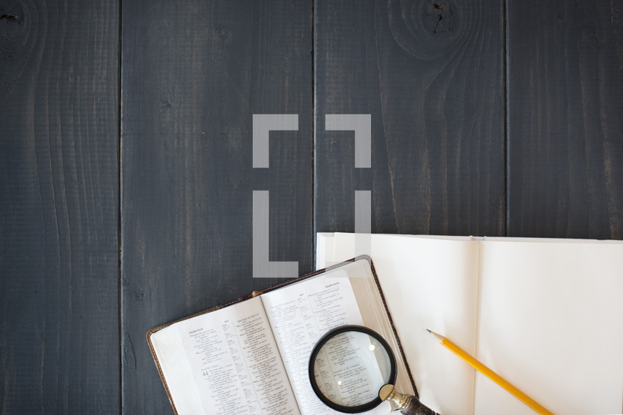 magnifying glass on the pages of a Bible and a journal and pencil