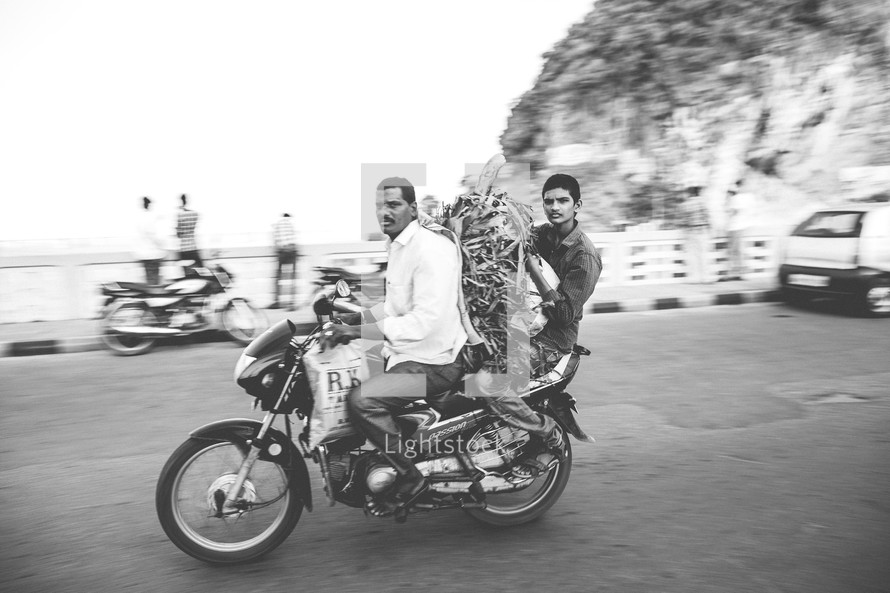 men carrying produce on a motorcycle in India