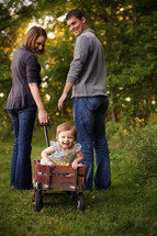 Mother, father, and daughter in a wagon.