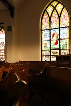 inside of old church with curved pews and stained glass windows