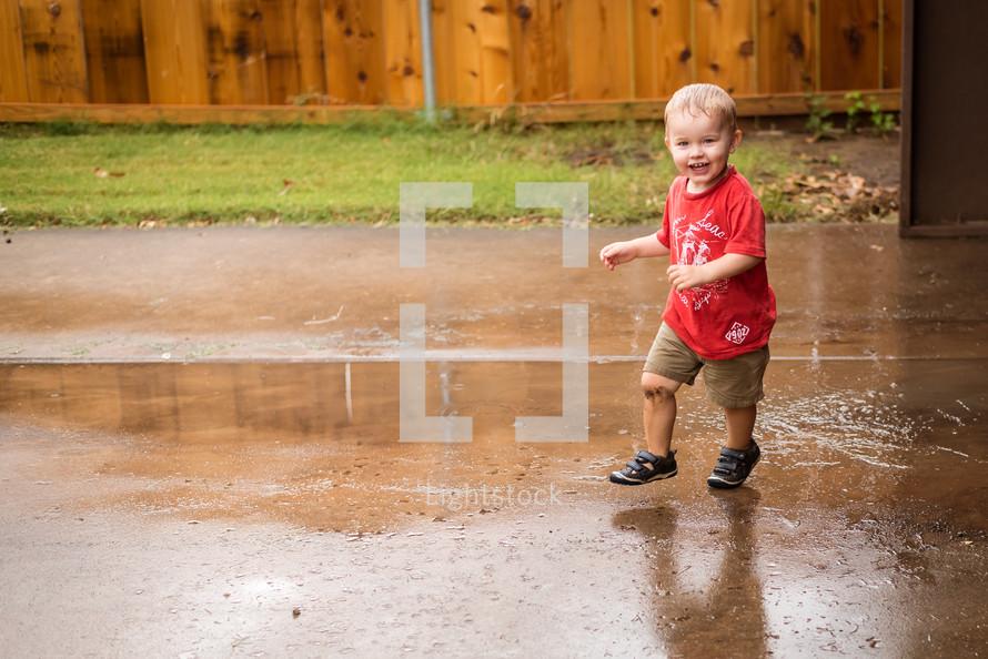 a toddler boy splashing in a puddle