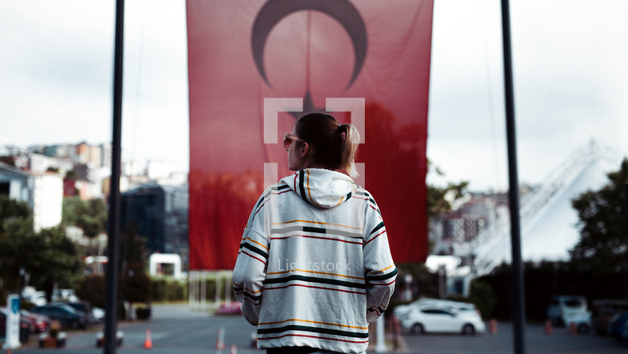 a woman standing in the street and the Turkish flag in the background