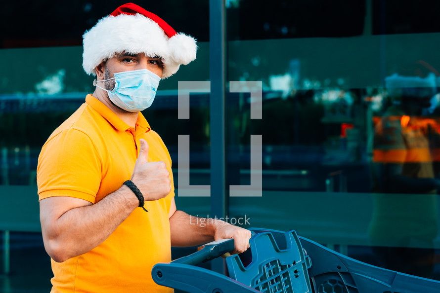 a man wearing a Santa hat and a mask with a shopping cart