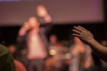 preacher giving a sermon and raised hands at a worship service