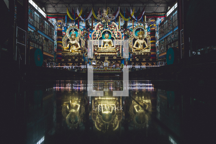 Golden statues inside of a Buddhist temple.