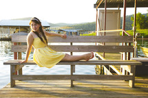 teen girl in a yellow sundress sitting on a bench
