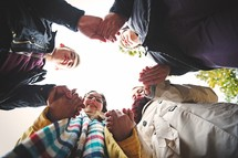 youth holding hands in a prayer circle