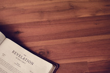 BIble on a wood floor opened to Revelation