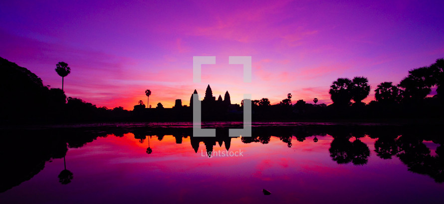 Sunrise over Angkor Wat reflected in water.