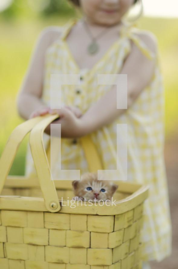 Girl holding basket with kitten