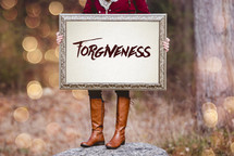a woman holding a sign the reads forgiveness