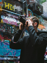 man taking a picture in a graffiti filled alley