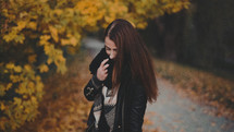 a brunette in a scarf standing outdoors in fall