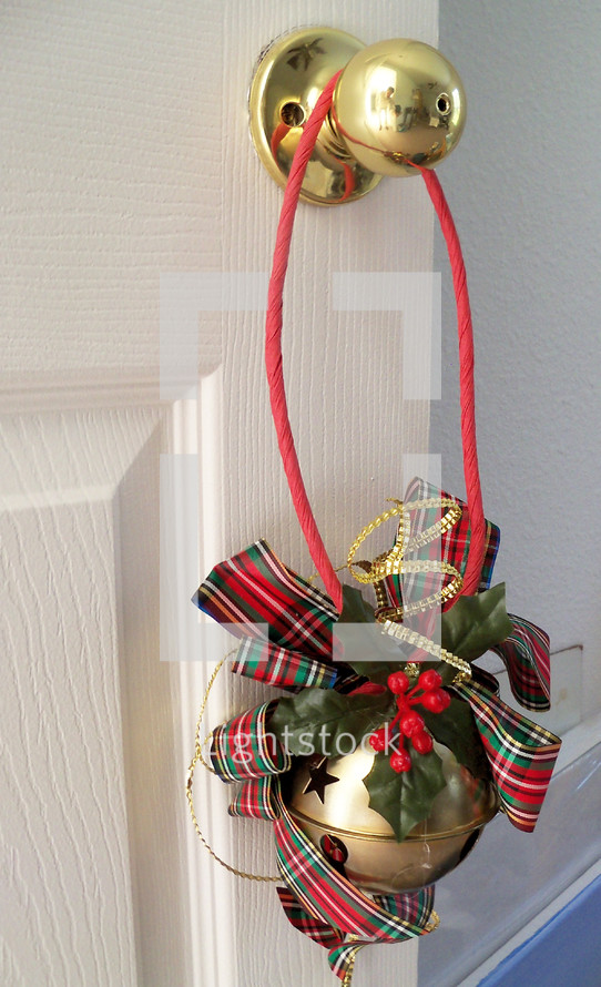 A big brass Jingle Bells with a red ribbon and red and green holly leaves adorn a brass door knob doorway entrance to a home's interior bringing out color, warmth and cheer for the Christmas holiday season.