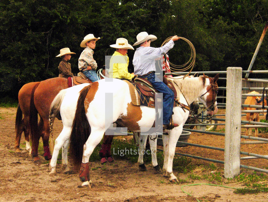 A group of young rodeo cowboys on horseback practicing their roping and riding skills at a rodeo in Central Florida where young cowboys and ranchers can practice and learn the skills to become cowboys.
