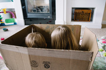 Two children playing in an empty box.