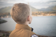 A young boy child taking in the view standing on a lake shore in fall.