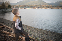 Young boy child in boots standing on a rocky shore pondering his life.