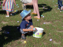 A young boy wearing a white and blue hat kneels down to pick up Easter Eggs among his friends and family at a church sponsored Easter Egg Hunt for children. Each year many churches gather the children and families of the community to have a church wide Easter Egg hunt and invite people to church.
