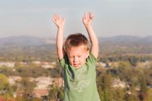 boy child with hands raised