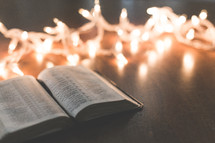 white Christmas lights and open Bible