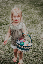 toddler girl carrying a basket of Easter eggs