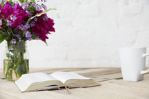 flowers in a vase, open Bible, and coffee mug on a table