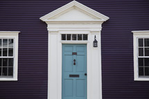 blue front door on a purple house
