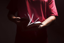 man flipping through the pages of a Bible in a dark room.