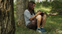 woman leaning against a tree reading a Bible