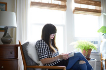 a woman sitting in a chair reading a Bible at home