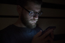 man looking at a cellphone screen in the dark.