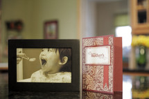 Happy Mother's day card and a framed photo of a mother feeding a baby