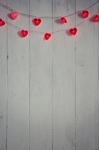 String of heart-shaped lights on a white wood background.