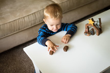 a toddler playing with a wooden nativity