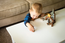 a toddler playing with wooden nativity figurines