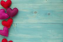border of felt hearts on teal wood