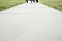 Family's feet walking down a sidewalk path.
