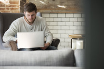man with a laptop sitting on a couch.