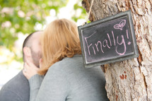 couple kissing in front of a sign with the words finally