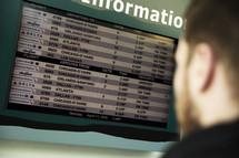 man looking at flight information at the airport