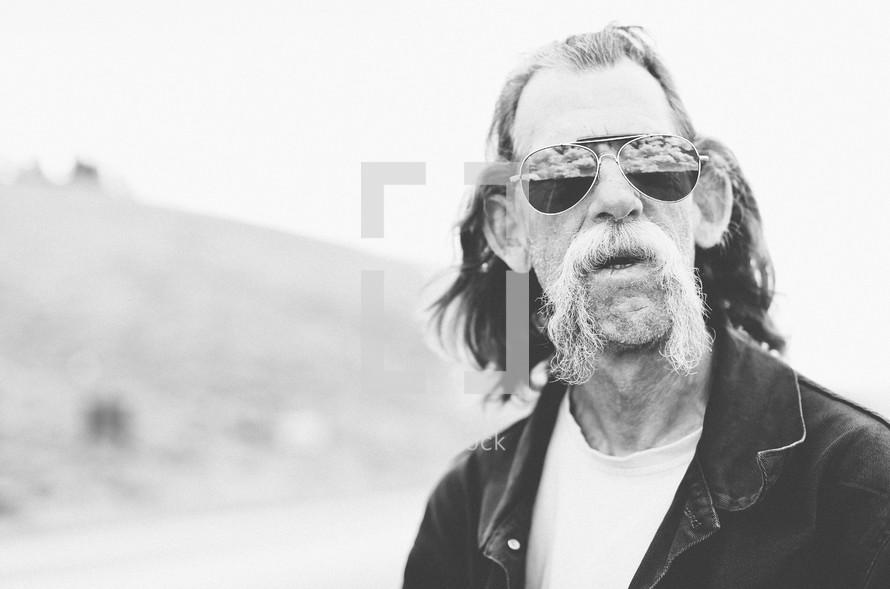 An elderly man with a handlebar mustache wearing sunglasses
