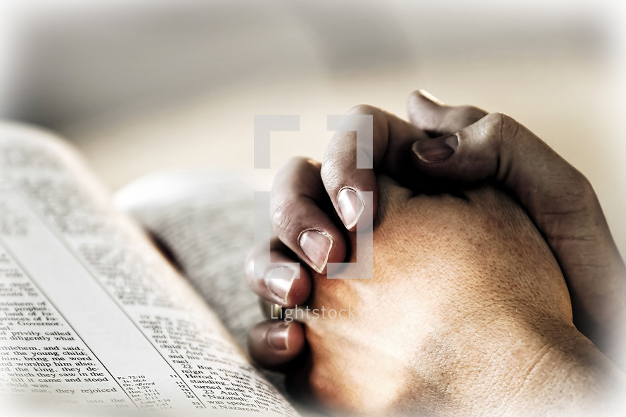 A man's hands clasped in deep prayer over a Holy Bible, while surrounded by light.