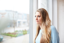 a woman standing in front of a window