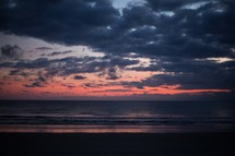 pink and purple clouds over a beach at sunset