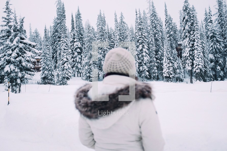 A woman in coat and hat standing before a snow covered forest.