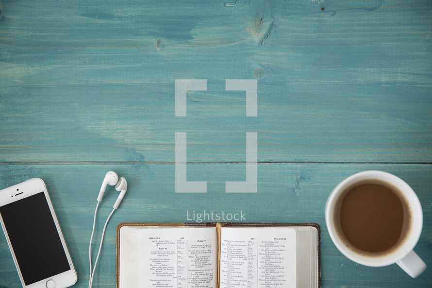 An open Bible, cellphone, ear buds, and cup of coffee on a green wooden table.